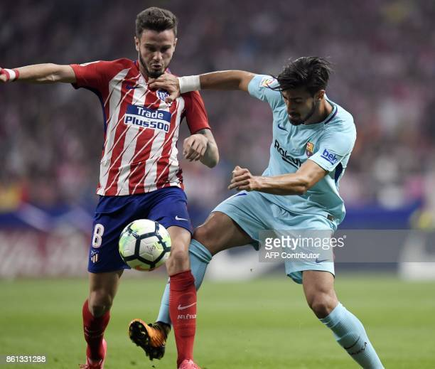 Atletico Madrid's Spanish midfielder Saul Niguez vies with Barcelona's Portuguese midfielder Andre Gomes during the Spanish league football match...