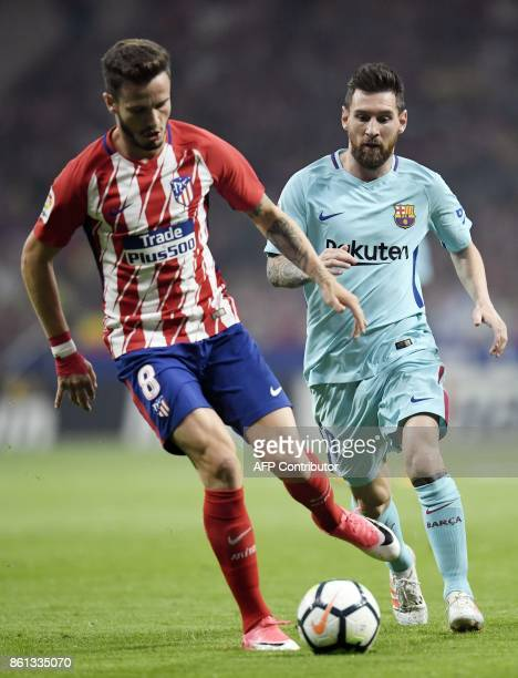 Atletico Madrid's Spanish midfielder Saul Niguez vies with Barcelona's Argentinian forward Lionel Messi during the Spanish league football match Club...