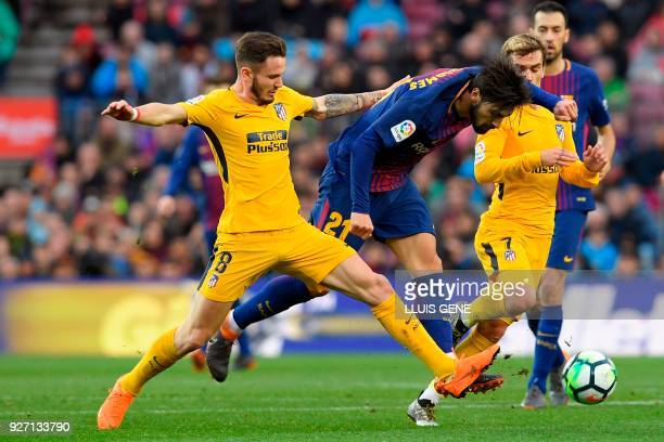 Atletico Madrid's Spanish midfielder Saul Niguez vies with Barcelona's Portuguese midfielder Andre Gomes during the Spanish league football match FC...