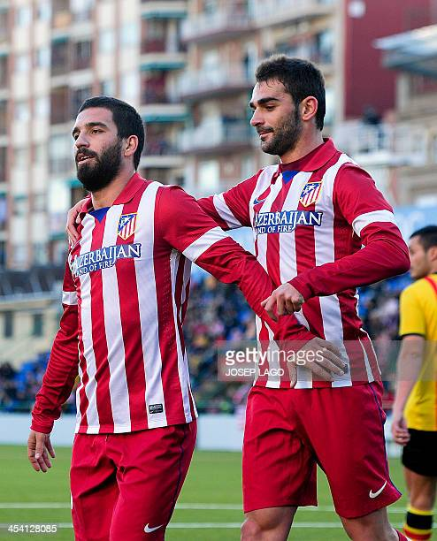 Atletico Madrid's Turkish midfielder Arda Turan is congratulated by his teammate Atletico Madrid's forward Adrian Lopez after scoring during the...