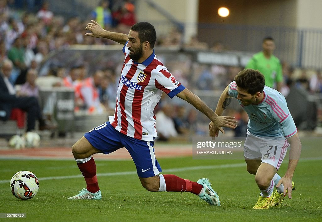 Atletico Madrid's Turkish midfielder Arda Turan (L) vies with Celta Vigo's defender Carles Planas during the Spanish league football match Club Atletico de Madrid vs Celta de Vigo at the Vicente Calderon stadium in Madrid on September 20, 2014.
