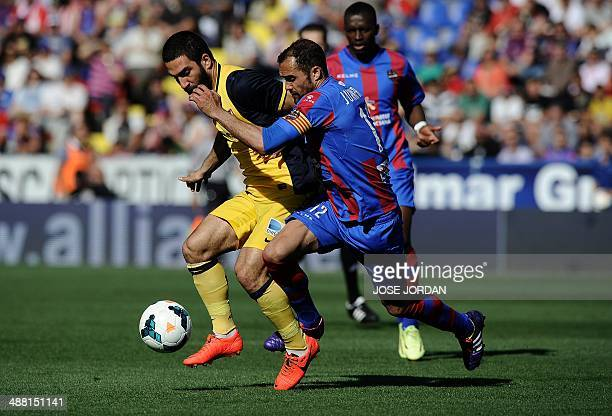 Atletico Madrid's Turkish midfielder Arda Turan vies with Levante's defender Juanfran during the Spanish league football match Levante UD vs Club...