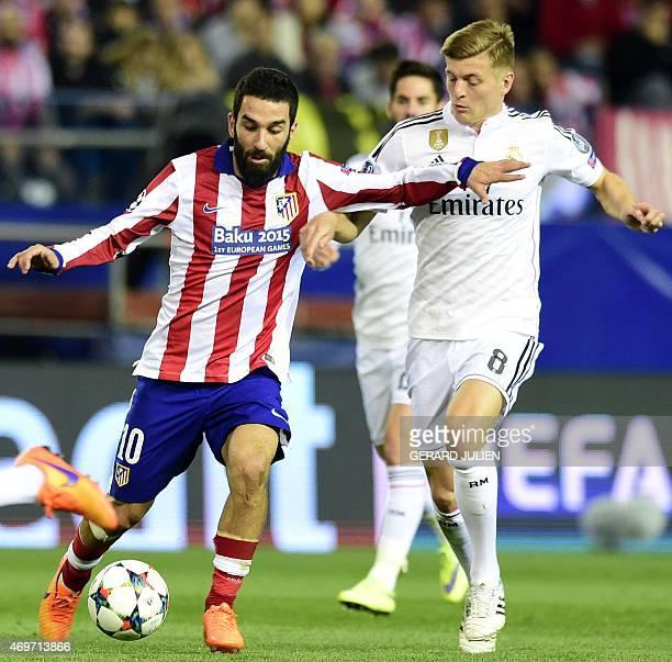 Atletico Madrid's Turkish midfielder Arda Turan vies with Real Madrid's German midfielder Toni Kroos during the UEFA Champions League quarter final...