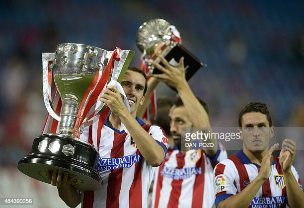 Atletico Madrid's Uruguayan defender Diego Godin and Atletico Madrid's midfielder Juanfran show off the 20132014 Spanish Liga Champions trophies...