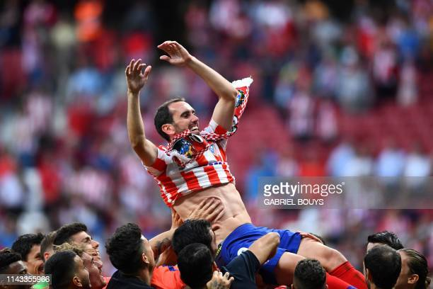 TOPSHOT Atletico Madrid's Uruguayan defender Diego Godin celebrates with teammates after the Spanish League football match between Atletico Madrid...