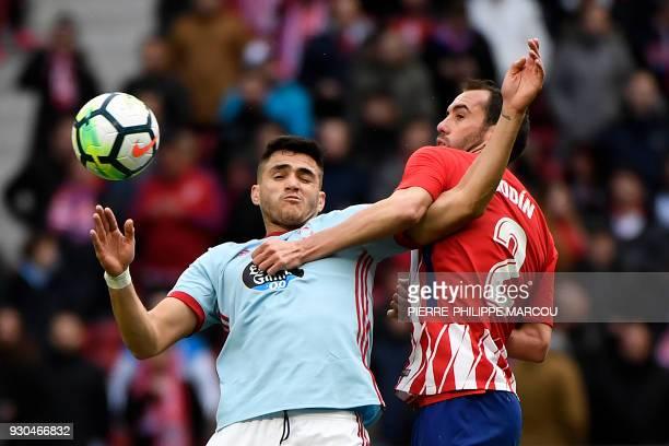TOPSHOT Atletico Madrid's Uruguayan defender Diego Godin challenges Celta Vigo's Uruguayan forward Maxi Gomez during the Spanish league football...