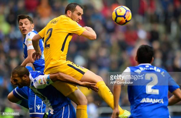 Atletico Madrid's Uruguayan defender Diego Godin jumps for the ball with Deportivo La Coruna's Costa Rican midfielder Celso Borges during the Spanish...