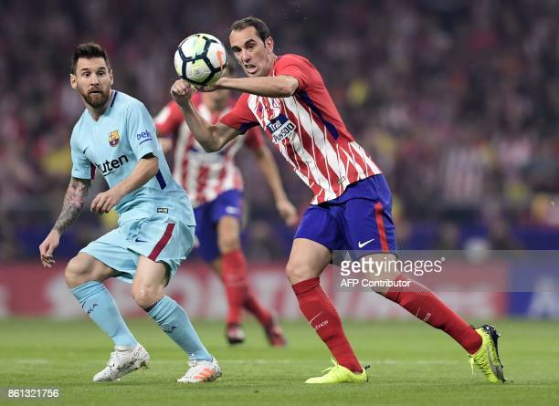 Atletico Madrid's Uruguayan defender Diego Godin vies with Barcelona's Argentinian forward Lionel Messi during the Spanish league football match Club...