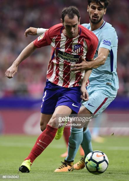 Atletico Madrid's Uruguayan defender Diego Godin vies with Barcelona's Portuguese midfielder Andre Gomes during the Spanish league football match...