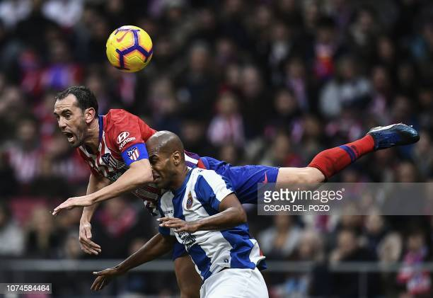 TOPSHOT Atletico Madrid's Uruguayan defender Diego Godin vies with Espanyol's defender Naldo during the Spanish League football match between Club...