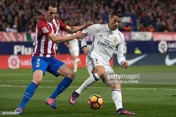 TOPSHOT Atletico Madrid's Uruguayan defender Diego Godin vies with Real Madrid's Portuguese forward Cristiano Ronaldo during the Spanish league...