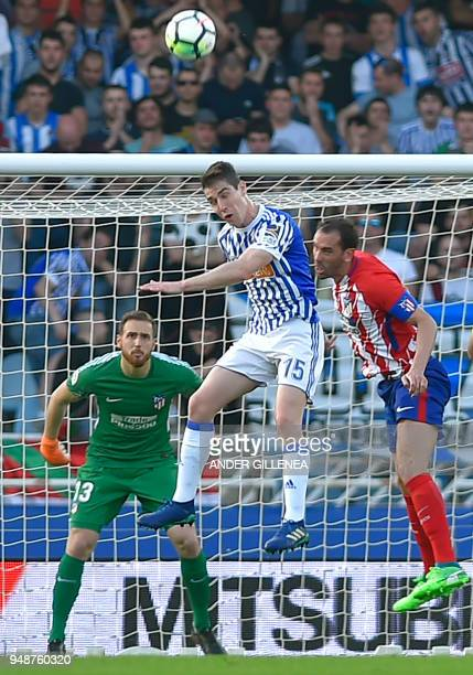 Atletico Madrid's Uruguayan defender Diego Godin vies with Real Sociedad's Spanish defender Aritz Elustondo during the Spanish league football...