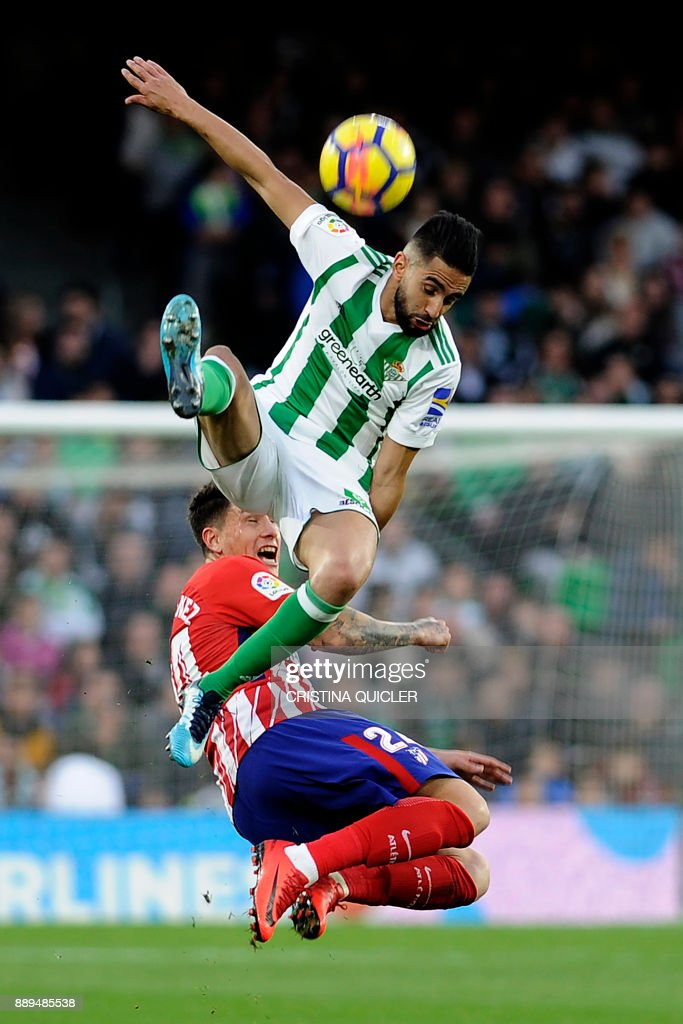 Atletico Madrid's Uruguayan defender Jose Maria Gimenez challenges Real Betis' Algerian midfielder Ryad Boudebouz (top) during the Spanish league football match between Real Betis and Atletico Madrid at the Benito Villamarin Stadium in Sevilla on December 10, 2017. /
