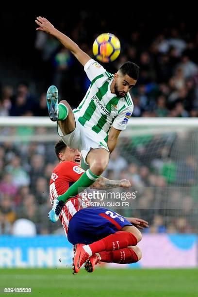 Atletico Madrid's Uruguayan defender Jose Maria Gimenez challenges Real Betis' Algerian midfielder Ryad Boudebouz during the Spanish league football...