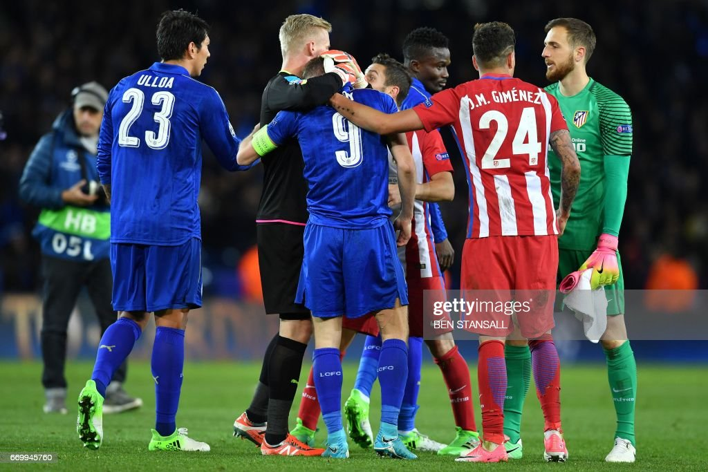 Atletico Madrid's Uruguayan defender Jose Maria Gimenez (R) consoles Leicester City's English striker Jamie Vardy (C) following the UEFA Champions League quarter-final second leg football match between Leicester City and Club Atletico de Madrid at the King Power stadium in Leicester on April 18, 2017. The match ended in a draw at 1-1, with Atletico Madrid winning on aggregate at 2-1. / AFP PHOTO / Ben STANSALL