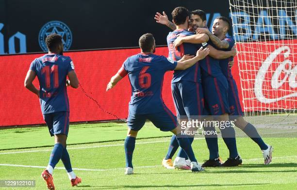 Atletico Madrid's Uruguayan forward Luis Suarez celebrates with teammates after scoring a goal during the Spanish League football match between Celta...