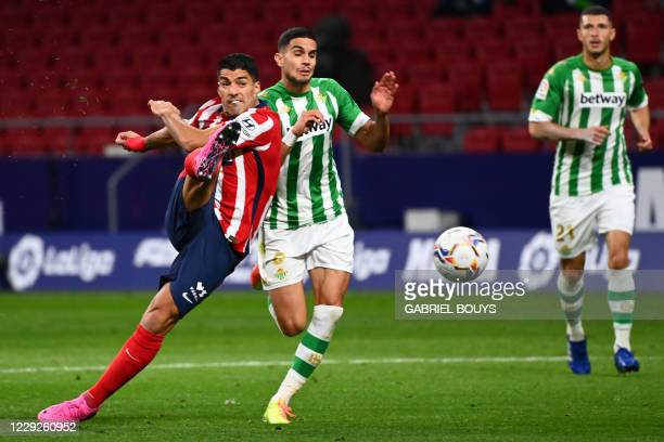 Atletico Madrid's Uruguayan forward Luis Suarez shoots beside Real Betis' Spanish defender Marc Bartra during the Spanish League football match...