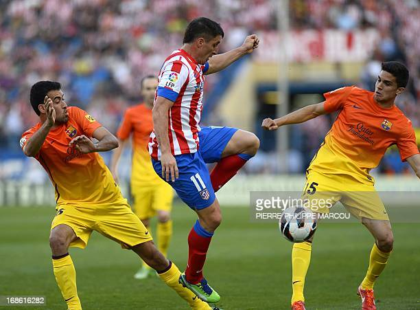 Atletico Madrid's Uruguayan midfielder Cristian Rodriguez vies with Barcelona's midfielder Sergio Busquets and Barcelona's defender Marc Bartra...