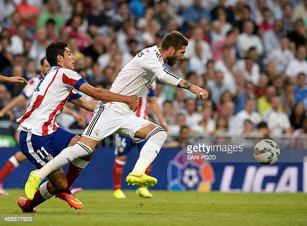 Atletico Madrid's Uruguayan midfielder Cristian Rodriguez vies with Real Madrid's defender Sergio Ramos during the Spanish league football match Real...