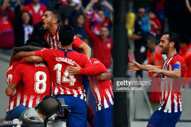 Atletico players celebrate their opening goal during the Spanish league football match between Club Atletico de Madrid and Real Betis at the Wanda...