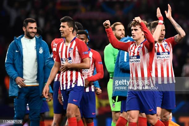 Atletico players celebrate their win at the end of the UEFA Champions League round of 16 first leg football match between Club Atletico de Madrid and...