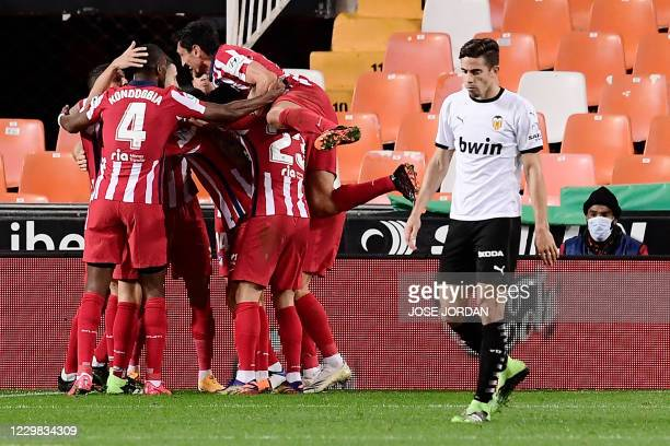 Atletico players celebrate Valencia's own goal during the Spanish League football match between Valencia and Atletico Madrid at the Mestalla stadium...