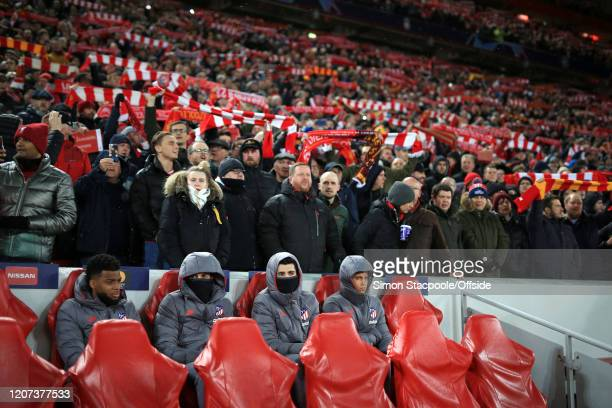Atletico substitutes sit on the bench surrounded by Liverpool fans during the UEFA Champions League round of 16 second leg match between Liverpool FC...
