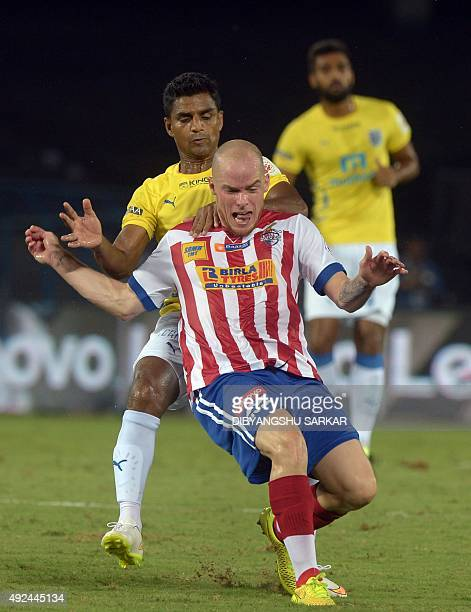 AtleticodeKolkata forward Iain Hume clashes with Kerala Blaster FC midfielder Mehtab Hossain during the Indian Super League football match between...