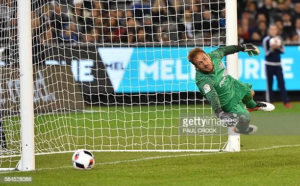 Atletico's keeper Jan Oblak dives to make a save during the International Champions Cup football match between English Premier League team Tottenham...