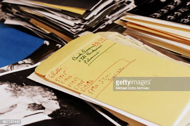 Atmosphere of the Michael Ochs Archives including piles of photos and an envelope that reads Buck Owens and the Buckaroos at the Palomino on May 10...