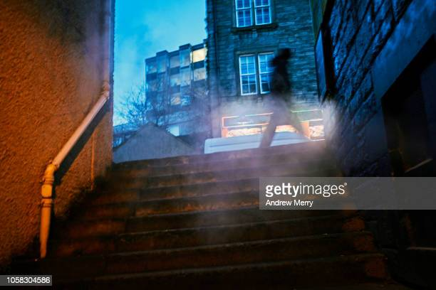 Atmospheric steam cloud in alley with blurred person walking through on footpath and blue night sky