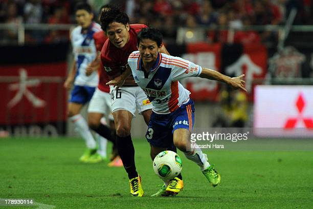 Atom Tanaka of Albirex Nigata and Ryota Moriwaki of Urawa Red Diamonds compete for the ball during the JLeague match between Urawa Red Diamonds and...
