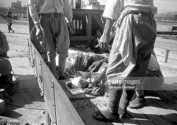 Atomic bomb survivers are carried by a truck to suburb of Hiroshima as their injuries seem not serious than others, on August 9, 1945 in Hiroshima,...