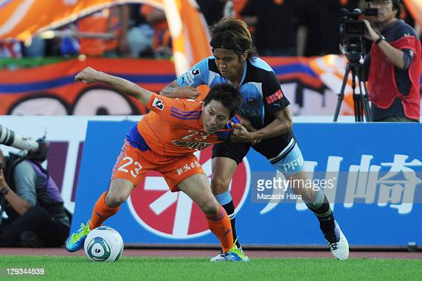 Atomu Tanaka of Albirex Niigata and Junichi Inamoto of Kawasaki Frontale compete for the ball during the JLeague match between Kawasaki Frontale and...
