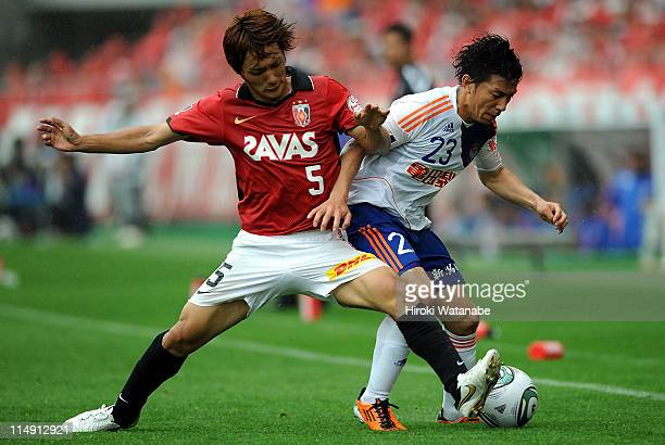 Atomu Tanaka of Albirex Niigata and Shunki Takahashi of Urawa Red Diamonds compete for the ball during JLeague match between Urawa Red Diamonds and...