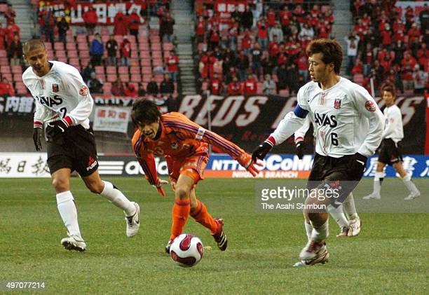 Atomu Tanaka of Albirex Niigata competes against Keisuke Tsuboi and Nobuhisa Yamada of Urawa Red Diamonds during he JLeague match between Albirex...