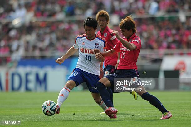 Atomu Tanaka of Albirex Niigata passes the ball under the challenge from Takumi Minamino of Cerezo Osaka during the J League match between Cerezo...