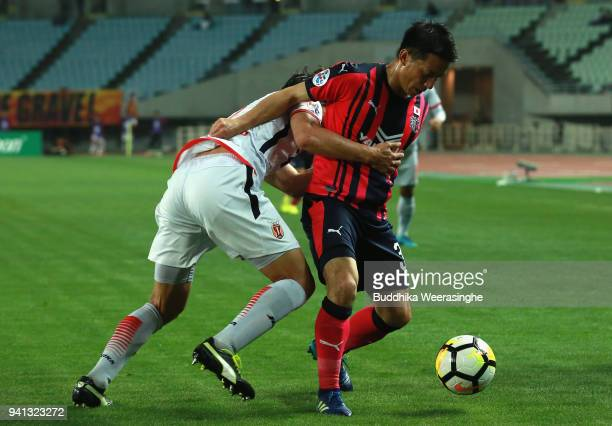 Atomu Tanaka of Cerezo Osaka controls the ball under pressure of Jung Dahwon of Jeju United during the AFC Champions League Group G match between...