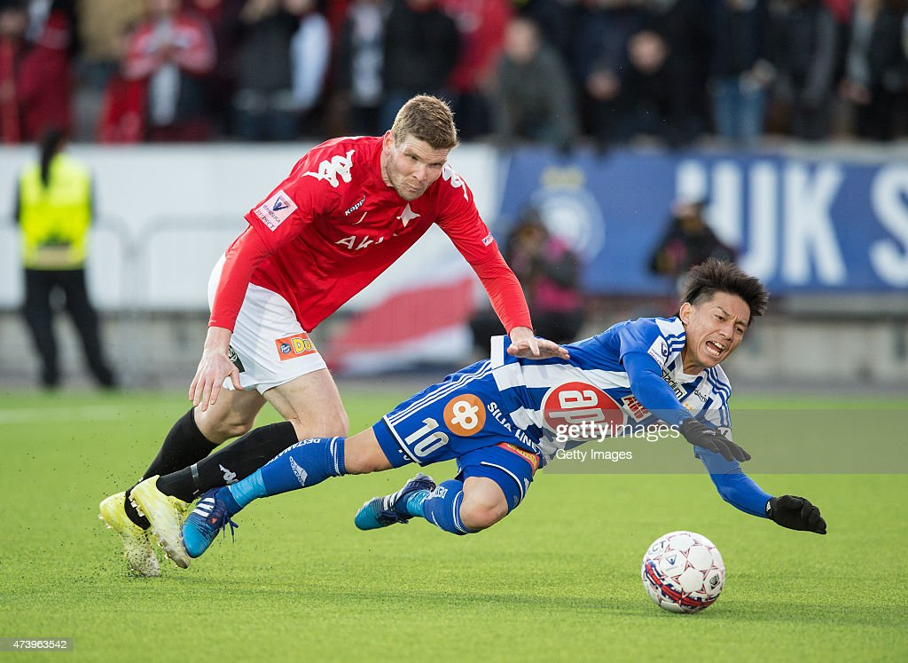 Atomu Tanaka of HJK Helsinki is tackled by Tuomas Aho of HIFK Helsinki during the Finnish First Division match between HJK Helsinki and HIFK Helsinki at Sonera Stadium on April 23, 2015 in Helsinki, Finland.