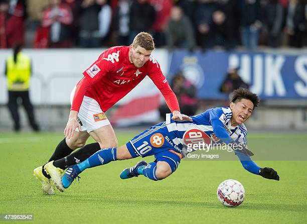 Atomu Tanaka of HJK Helsinki is tackled by Tuomas Aho of HIFK Helsinki during the Finnish First Division match between HJK Helsinki and HIFK Helsinki...
