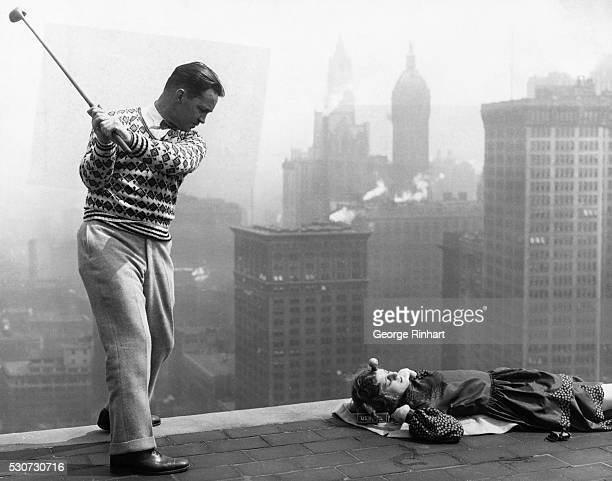 Atop the Whitehall building in New York world Champion trick shot golfer Jack Redmond demonstrates his golfing skill by teeing off from Miss Muriel...