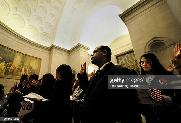 Atra Osman of Ethiopia, center, and Flor Silva of El Salvador take the Oath of Allegiance with others during a naturalization ceremony of 215 people...
