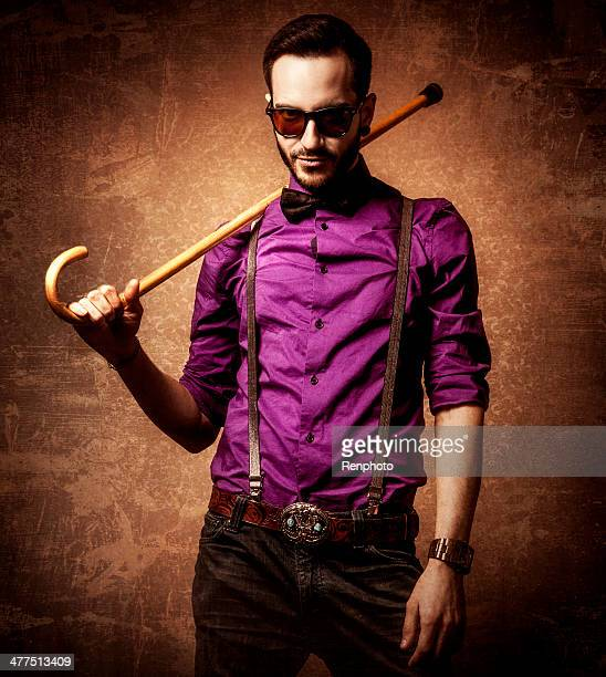 atractive man wearing sunglasses and holding a cane - purple suit stock pictures, royalty-free photos & images