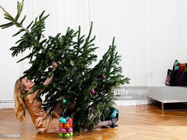 atractive young woman holds a christmas tree up