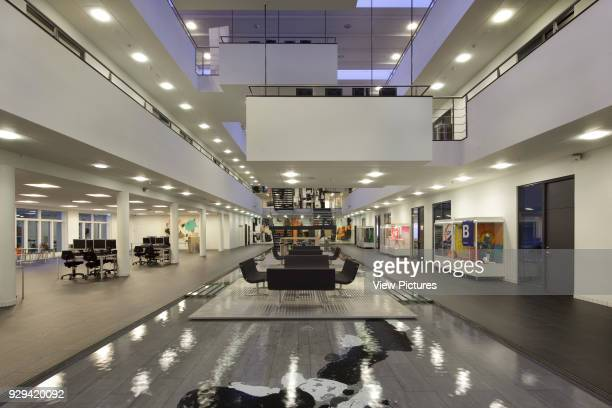 Atrium with water feature and meeting area seen from ground floor at dusk IBC Kolding Campus Kolding Denmark Architect schmidt hammer lassen...
