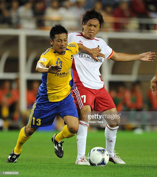 Atsushi Yanagisawa and Yasuhito Endo compete for the ball during the JLeague Special Match at Kashima Soccer Stadium on July 21 2012 in Kashima...