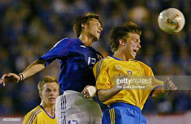 Atsushi Yanagisawa of Japan and Anders Svensson of Sweden compete for the ball during the international friendly match between Japan and Sweden at...