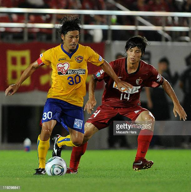 Atsushi Yanagisawa of Vegalta Sendai and Chikashi Masuda of Kashima Antlers compete for the ball during the JLeague match between Kashima Antlers and...