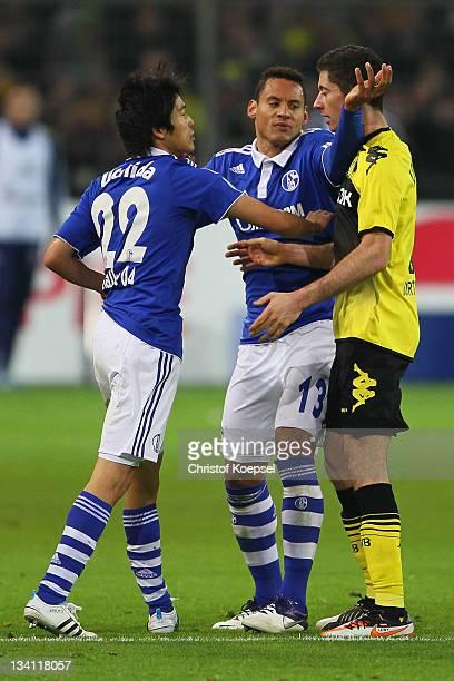 Atsuto Uchida and Jermaine Jones of Schalke attack Robert Lewandowski of Dortmund during the Bundesliga match between Borussia Dortmund and FC...