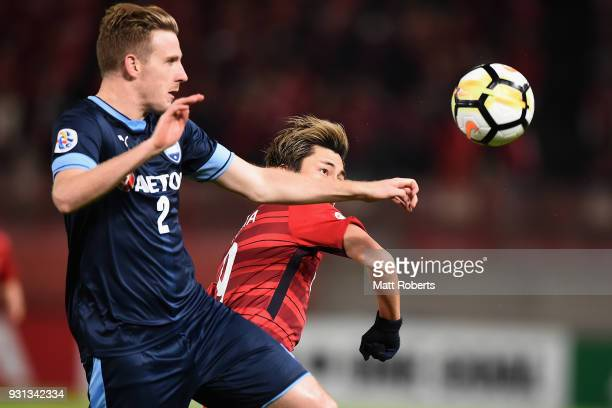 Atsuto Uchida of Kashima Antlers competes for the ball against Aaron Calver of Sydney FC during the AFC Champions League Group H match between...